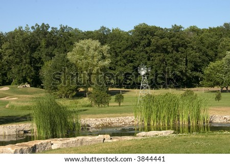Country Land With Windmill & Pond - stock photo