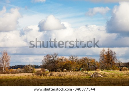 Country landscape scenic with village in background on sunny cloudy day in autumn in Belarus - stock photo