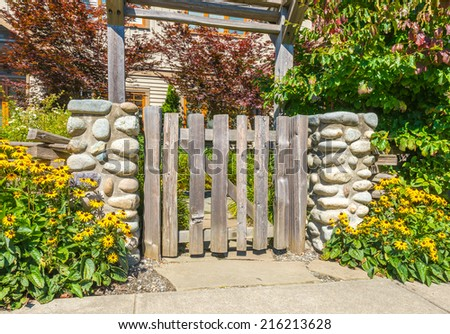 Country looking wooden gates at front, back yard. Flowers and stones as an elements of landscape design. - stock photo