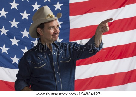Country man pointing to crowd in front of American flag, horizontal