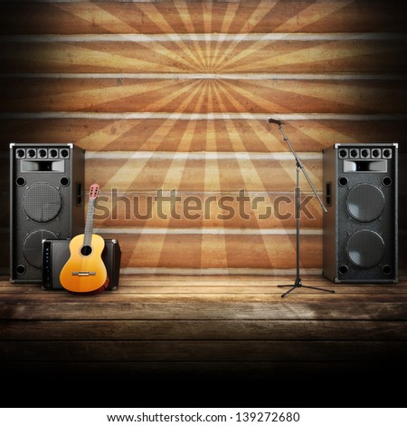 Country music stage or singing background, microphone, guitar and speakers with wood flooring and sunburst background. Advertising concept with room for text or copy space - stock photo