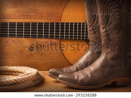 Country music with guitar and cowboy shoes on wood texture background - stock photo