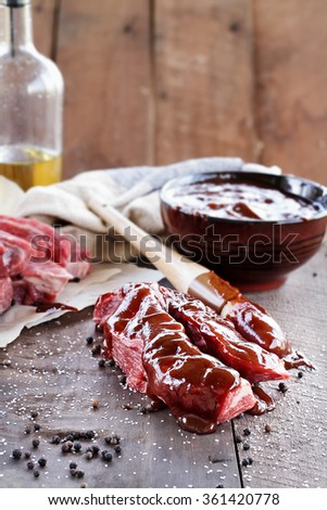 Country ribs with barbecue sauce and basting brush over a rustic table.  - stock photo