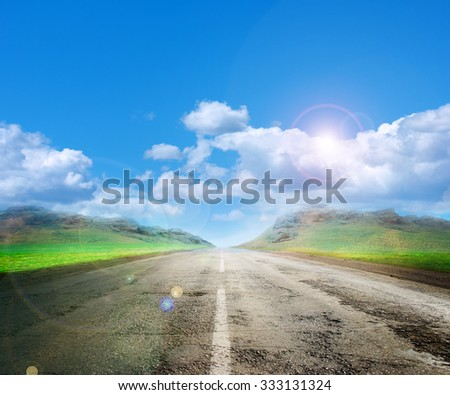 country road among the plain and sunny sky