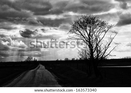 Country road and dramatic sky - stock photo