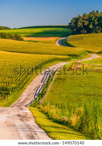 Country road and farm fields on a large hill in rural York County, Pennsylvania. - stock photo