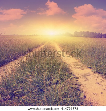 Country road at sunset in vintage style. - stock photo