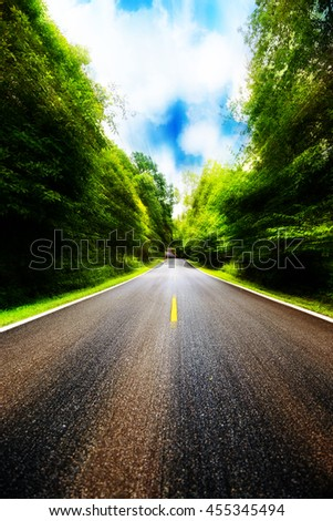 Country road between district to the city with motion blur, Journey way of traveler to the nature, Road in the mountain and the forest for travel to someplace, Asphalt road in the forest and no car.