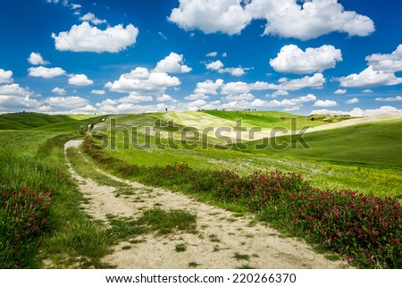 Country road between green hills - stock photo