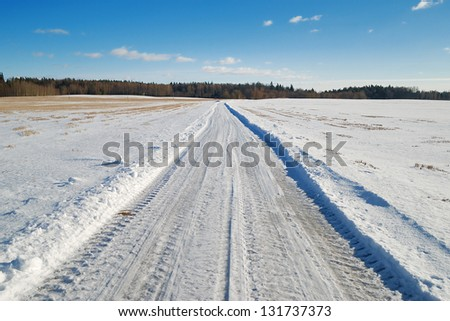 Country road covered in snow in a field