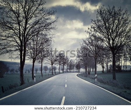 Country Road in Autumn - Country road in autumn leading through a mountain landscape  - stock photo