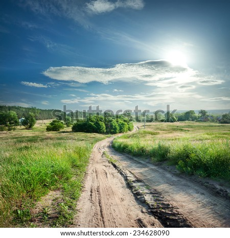 Country road in field with green grass under a dramatic sky - stock photo
