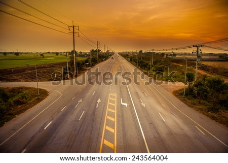 country road in Thailand with the last light of the day - stock photo