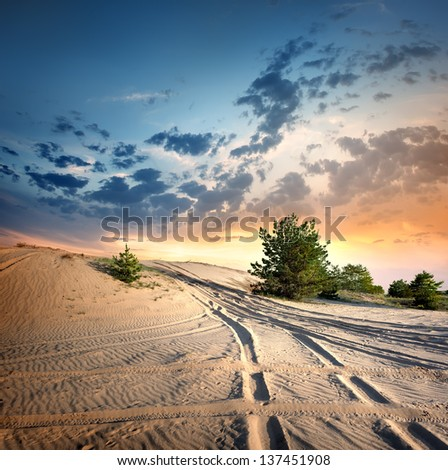 Country road in the desert at sunset - stock photo