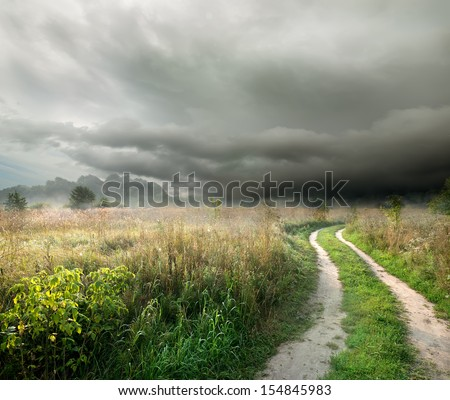 Country road in the field on a background of thunder clouds