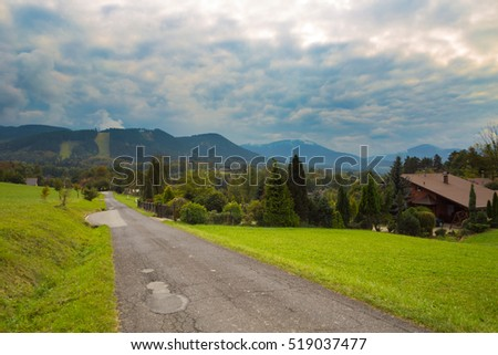 Country road in the mountain village with a cloudy sky in Moravian-Silesian Beskydy