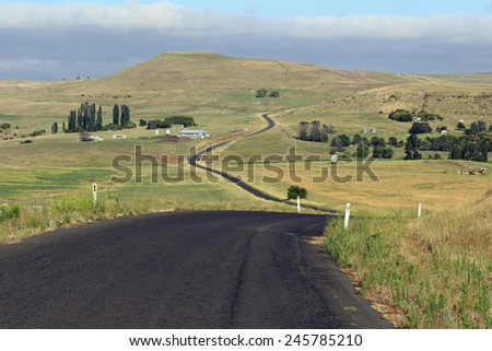 Country road leading up into the hills near Dalgety, NSW, Australia - stock photo