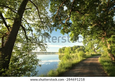 Country Road on the shore of the lake in spring morning. - stock photo