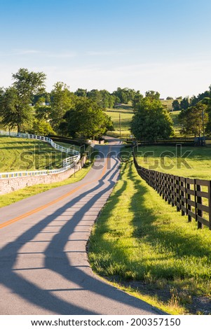 Country road surrounded the horse farms with evening fence shadows. - stock photo