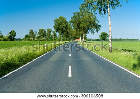 Country-road through northern German lowlands with green fields and trees on a sunny day; Cross-country trip - stock photo