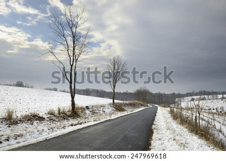 Country Road Through Snow Covered Fields - stock photo