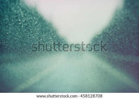 country road through the windshield during rain, vintage retro style