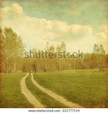 Country road to forest in grunge and retro style. - stock photo