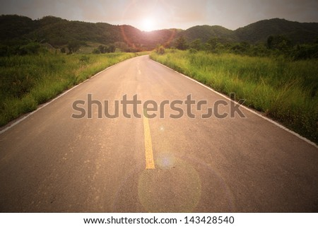Country road to mountain with sun flare in concept go to target go to your destination - stock photo