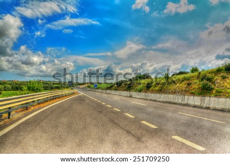 country road under a scenic sky in hdr tone mapping effect - stock photo