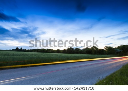 Country road with car light strips at dusk - stock photo