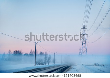 Country road with electricity pylons on foggy winter evening - stock photo