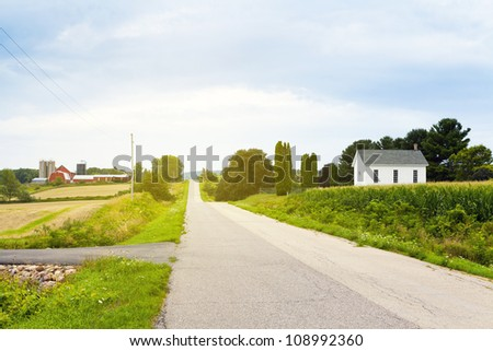 Country Road With Red Farm and Church - stock photo