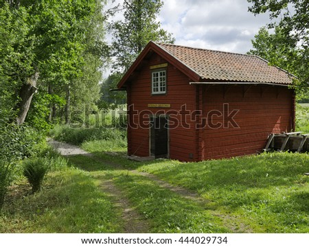 Country road with red house in a midsummer day - stock photo
