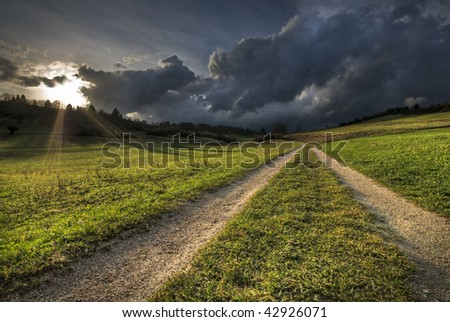 Country Road with sun shining through Rainy Clouds