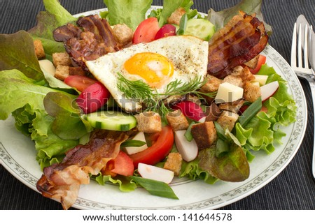 Country salad also called peasant salad, greek salad or village salad. Composed with lettuce, cucumber, onion, radish, fried egg and bacon, cheese, tomatoes, parsley and croutons.