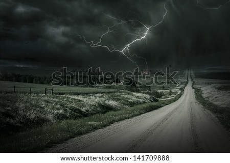 Country Storm. Back Country Gravel Road and Storm Ahead. Lightning Bolt in a Distance. Severe Weather Collection. - stock photo