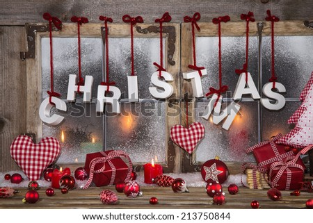 Country style christmas decoration in red, white and wood on an old window. - stock photo