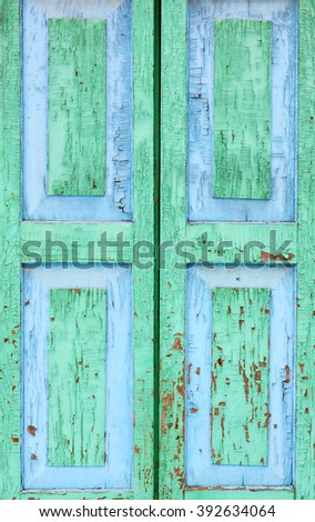 Country style. Detail of an old window. Peeling paint green and blue color on the wooden shutters. The texture of old wood as background.  - stock photo