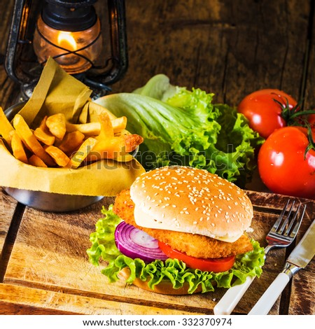 Country-style dish on a wooden table with a chicken burger and fried chips - stock photo