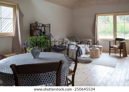 Country style interior of a living room with a round dining table - stock photo