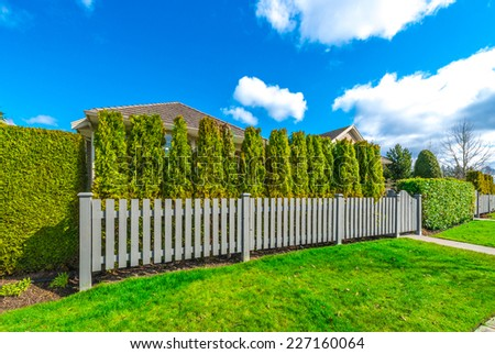 Country style long wooden fence with nicely trimmed grass. - stock photo