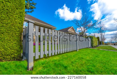 Country style long wooden fence with the gate, wicket and a house behind. Country style long wooden fence with nicely trimmed grass.