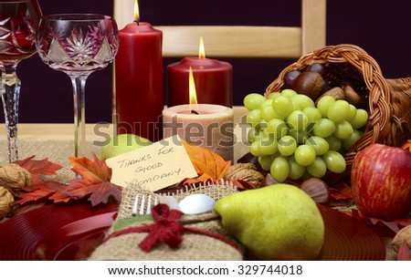 Country style, rustic Thanksgiving table place setting closeup with chair, cornucopia, wine glasses, fruit, nuts and burning candles.   - stock photo