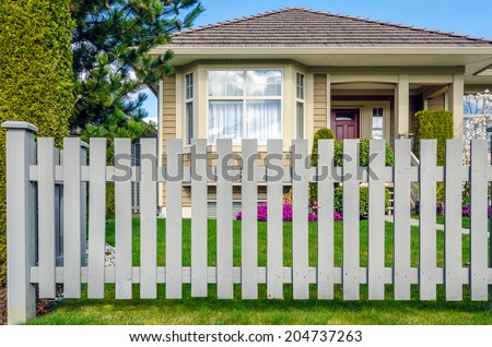 Country style wooden fence with a beautiful house behind. Exterior design.