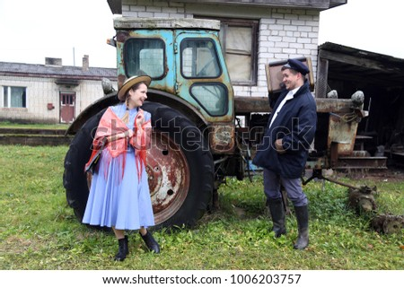Country style young woman and man stand happy laughing outdoor on old half disassembled tractor background - peasant lifestyle
