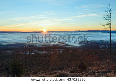 Country sunrise view with sun, colorful sky and clouds over foothills.