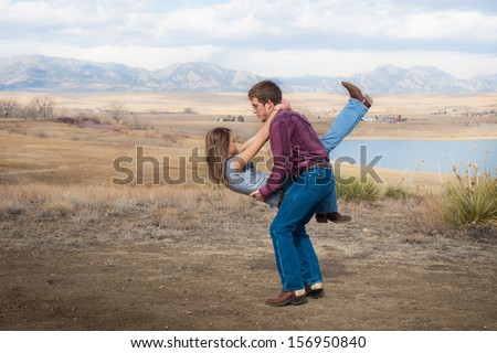 Country swing dancing at the foothill of mountains. - stock photo