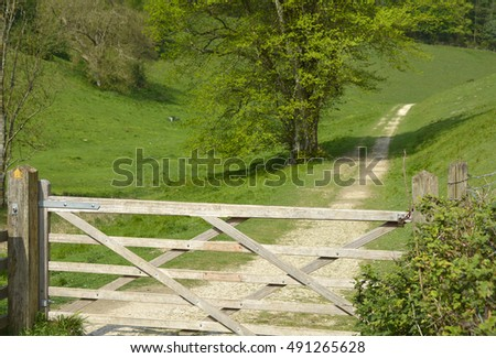Country track with a five bar gate across it. West Sussex, England