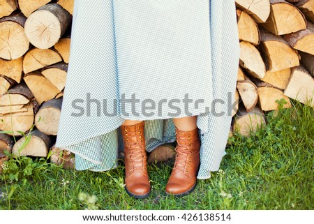 country wedding, bride in brown shoes near logs - stock photo