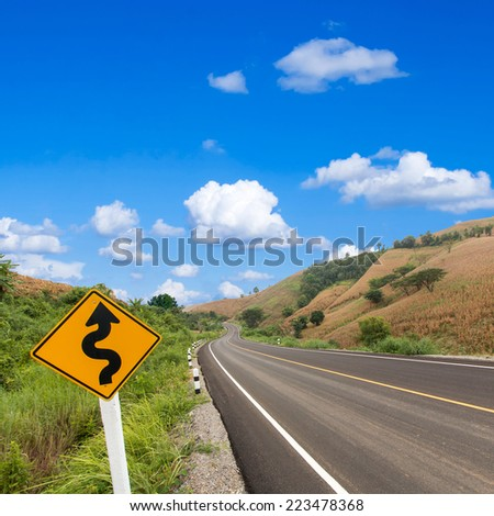 country winding road sign with blue sky - stock photo